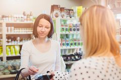 Woman paying with contactless credit card. In shop Royalty Free Stock Photos
