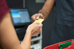 Woman paying with credit card. Close up of customer's hand giving credit card to cashier at checkout. Woman using credit card to pay at supermarket. Woman Royalty Free Stock Images