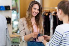 Woman paying with credit card in clothing store Stock Images