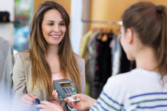 Woman paying with credit card in clothing store Royalty Free Stock Image