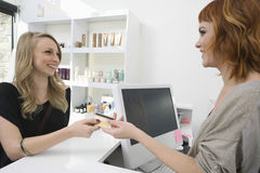 Woman Paying Through Credit Card At Hair Salon Stock Photo