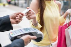 Woman paying credit card with payment terminal and cashier man Stock Photos