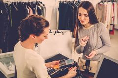 Woman paying with credit card in s showroom. Happy women customer paying with credit card in fashion showroom Royalty Free Stock Image