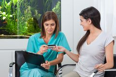 Woman Paying Through Credit Card To Dentist Royalty Free Stock Image