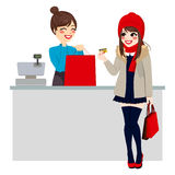 Woman Paying With Credit Card. Young beautiful brunette woman paying purchase with credit card while store clerk is preparing shopping bag royalty free illustration