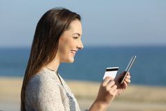 Woman paying on line with credit card on the beach. Side view portrait of a happy woman paying on line with credit card on the beach Royalty Free Stock Photos