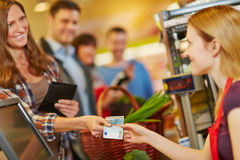 Woman paying with money at supermarket checkout. Smiling women paying with Euro money bill at supermarket checkout stock photo