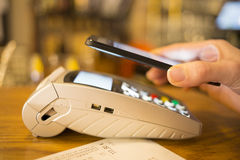 Woman paying with NFC technology on mobile phone,  Royalty Free Stock Photography
