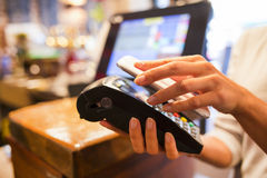 Woman paying with NFC technology on mobile phone, restaurant, ca Royalty Free Stock Images