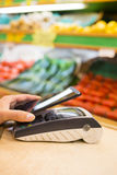 Woman paying with nfc technology on mobile phone, shopping, supe Royalty Free Stock Image