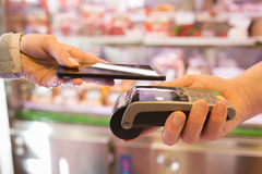 Woman paying with NFC technology on mobile phone, in supermarket Royalty Free Stock Photos