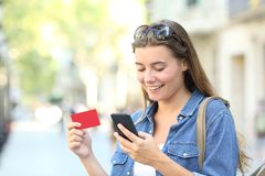 Woman paying online with a credit card outdoors. Happy woman paying online with a credit card and a smart phone outdoors in the street Royalty Free Stock Photo