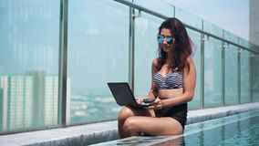 Woman paying online in the pool on a sunny day stock footage