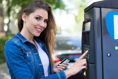 Woman paying for parking Stock Photography