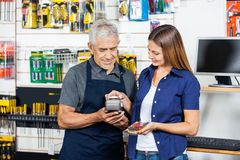Woman Paying Through Smartphone In Hardware Store Royalty Free Stock Photos