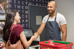 Woman paying at supermarket. Happy women at checkout of grocery store paying with credit card to cashier. Smiling women paying with her EC card at supermarket Stock Image