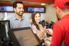 Woman paying for tickets on a date. Portrait of a good looking Hispanic couple on a date at the movie theater while the women pays for the tickets Stock Images