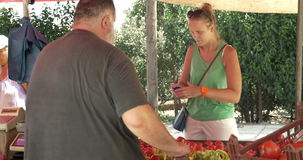 Woman paying for vegetables on the market stock footage