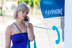 Woman on a payphone. Woman talking on a payphone in the street Royalty Free Stock Photos