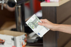 Woman pays cash for the breakfast in the cafe with euro banknotes. Stock Photography