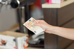 Woman pays cash for the breakfast in the cafe with euro banknotes. Royalty Free Stock Images