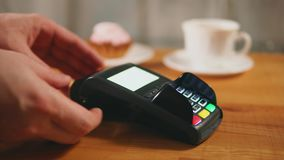 A woman pays coffee and dessert with a bank card, a contactless payment method. Close up shot of woman hands, who pays coffee and dessert by credit card stock video