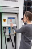 Woman pays at an electric car charging station royalty free stock photography