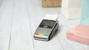 Woman pays with NFC technology on a bank card. Payment terminal on white wooden background. Gift boxes and Point of Sale Terminal or POS with receipt. Copy stock footage