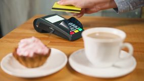 A woman pays a sweet breakfast with a contactless plastic card payment stock video footage