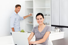 Woman on the pc while her husband preparing coffee Royalty Free Stock Photos