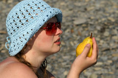 Woman and pear. Young woman holding a pear on the beach Stock Images