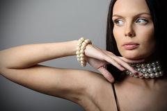 Woman with pearl. Beautiful brunette woman with pearl jewelry over gray background Royalty Free Stock Photography