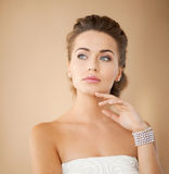 Woman with pearl earrings and bracelet. Beautiful bride wearing pearl earrings and bracelet royalty free stock photos
