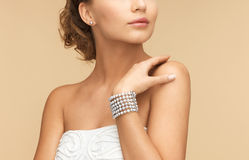 Woman with pearl earrings and bracelet. Beautiful bride wearing pearl earrings and bracelet stock photography