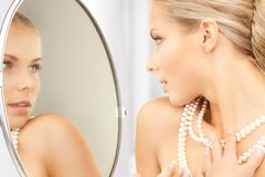 Woman with pearl necklace. Looking in the mirror Royalty Free Stock Photography