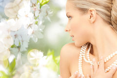 Woman with pearl necklace over cherry blossom Royalty Free Stock Image