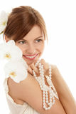Woman with pearls. Portrait of young woman with pearls and orchid isolated on white background royalty free stock image
