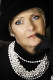 Woman in pearls and hat royalty free stock photography