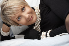 Woman in pearls in her 40s. Beautiful happy woman in her mid 40s with blond short hair wearing fresh water pearls resting in bed Royalty Free Stock Photos