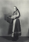 Woman in peasant dress carrying basket Stock Photos