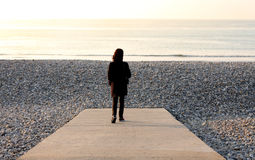 Woman on Pebble beach. Woman on a Pebble beach in the Somme bay in France Royalty Free Stock Photos