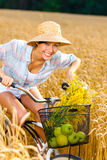 Woman pedals bicycle with apples and flowers Stock Photo