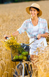 Woman pedals cycle with apples and flowers in rye field Royalty Free Stock Photo