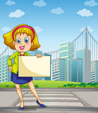 A woman at the pedestrian lane holding an empty signage Royalty Free Stock Photos