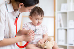 Woman pediatrician examining of baby kid with stethoscope Royalty Free Stock Photos