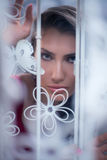 Woman peek out from behind white curtain near the window Royalty Free Stock Image