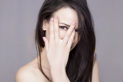 Woman peeking. Beautiful woman peeking through her fingers, on a white background Royalty Free Stock Photos