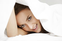 Woman peeking through bed sheets Royalty Free Stock Photos