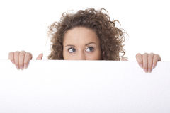 Woman peeking behind emtpy billboard. Young woman peeking behind empty white billboard Stock Photo