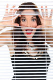 Woman peeking through blinds Royalty Free Stock Images